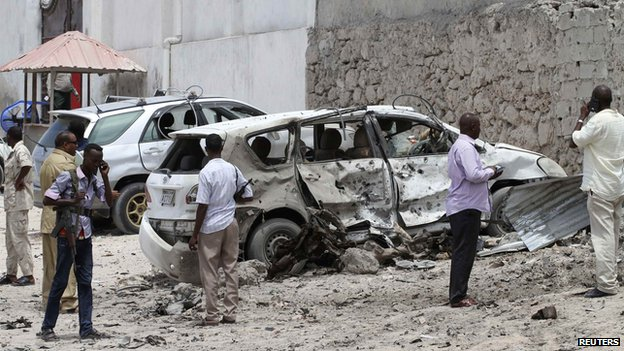 Somali security officers inspect a damaged car at the scene of an explosion near the Al Mukaram hotel in Mogadishu