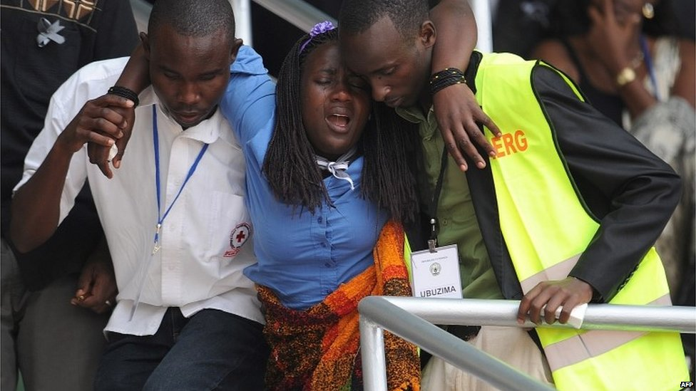 "A woman is helped out of the Amahoro stadium, in Kigali, on April 7,2014, during a ceremony marking the 20th anniversary of Rwanda""s genocide"