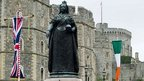 The Irish flag and the Union Flag are displayed on the roads next to a statue of Queen Victoria near Windsor Castle