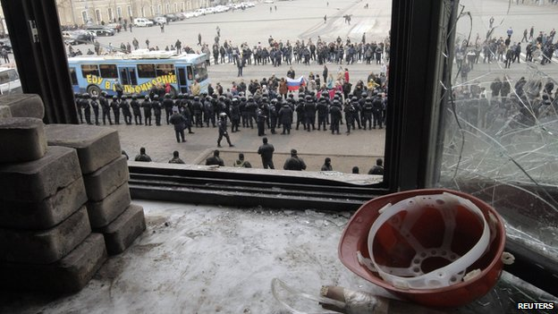 A view through a broken window of the regional administration building shows a cordon of Interior Ministry members blocking a group of pro-Russia protesters in Kharkiv