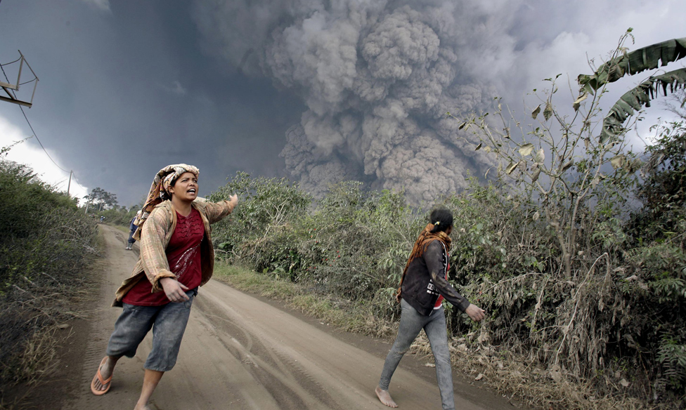 Villagers flee a volcano on Sumatra
