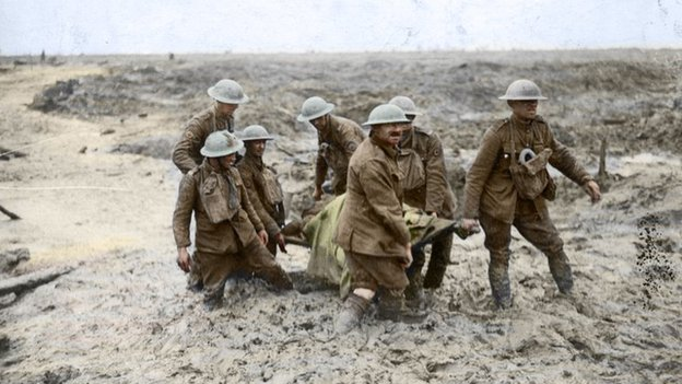 soldiers carrying stretchers and heavy equipment through a muddy battlefield
