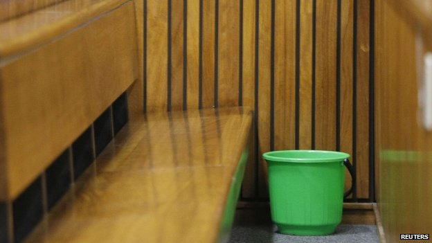 A bucket on the floor in the dock at the Pretoria High Court, 8 April 2014