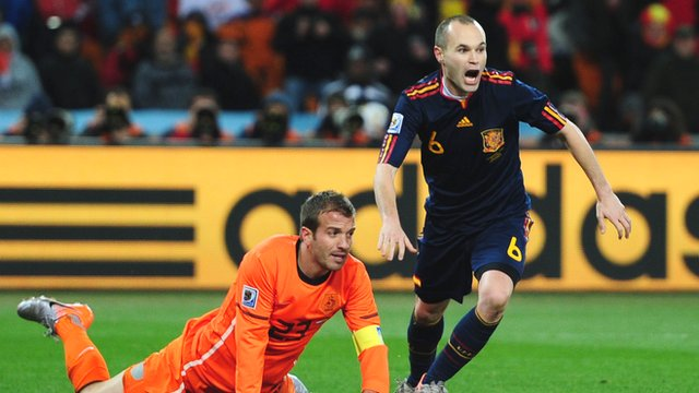 Andres Iniesta scores for Spain as Rafael van der Vaart of Netherlands looks on