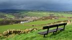 Grey cloud over a village and green fields. A bench in the foreground.