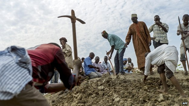 People dig as they bury 16 people in a Muslim cemetery in Bangui on 11 December 2013