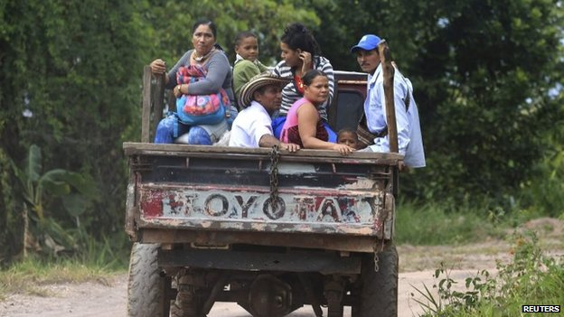 Coffee growers and their families, displaced by the conflict with Farc rebels, travel past a plantation in Serrania de Perija on 28 January, 2014