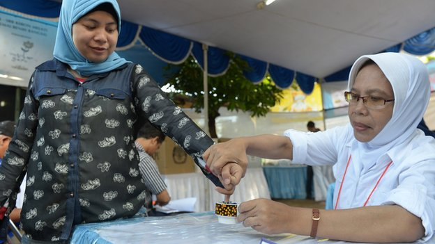 An Indonesian woman (L) has her finger inked after casting her ballot paper during legislative polls in Jakarta on 9 April 2014