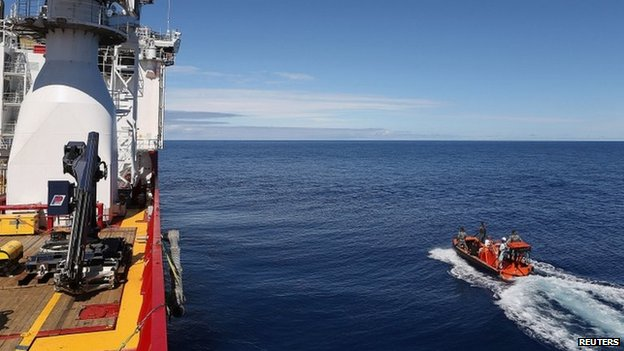 Crew members are seen aboard a fast response craft (R) from the Australian Defence Vessel Ocean Shield (L) as they continue to search for debris of MH370 in the southern Indian Ocean on 8 April 2014