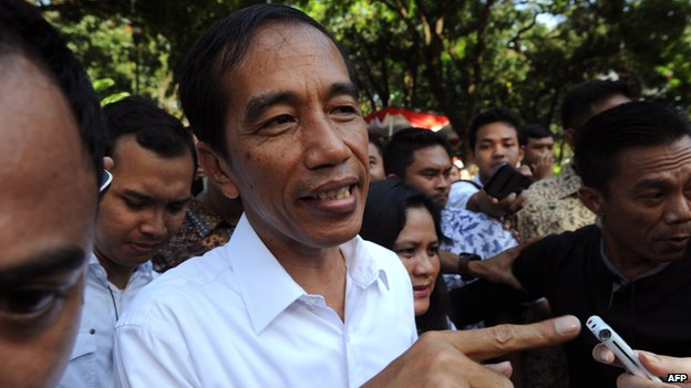 Jakarta Governor Joko Widodo and presidential candidate of the opposition Indonesian Democratic Party of Struggle (PDI-P) speaks to journalists after voting at a polling centre during the legislative election in Jakarta on 9 April, 2014