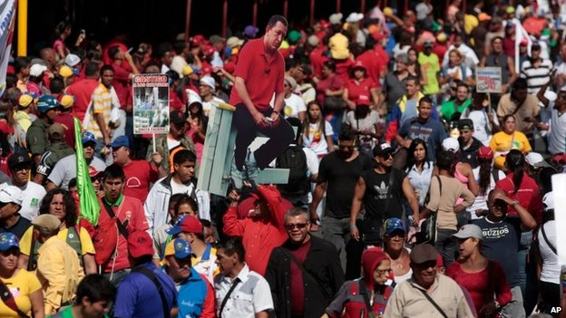 A man holds a cut-out of Venezuela's late President Hugo Chavez among a crowd of pro-government supporters in Caracas on 22 March, 2014