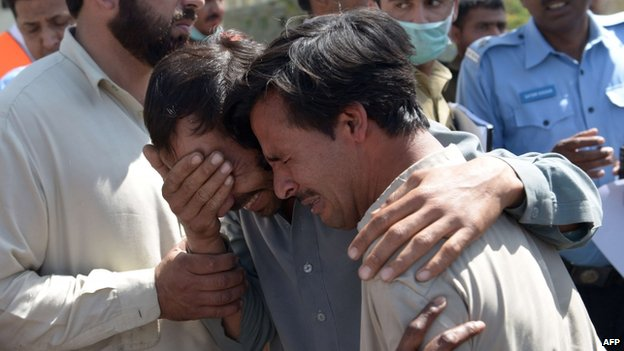 Pakistani mourners grieve the death of relatives at a hospital in Islamabad on 9 April 2014