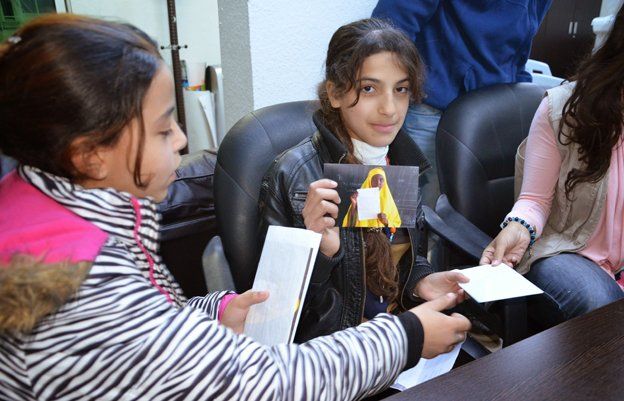 A Syrian girl holds a photo of a Somali refugee who has sent her a letter