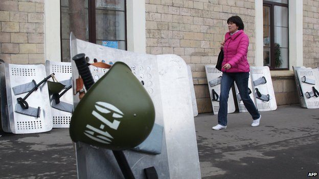 A woman walks through policemen's shields not far from the regional administration building in Kharkiv on 9 April 2014