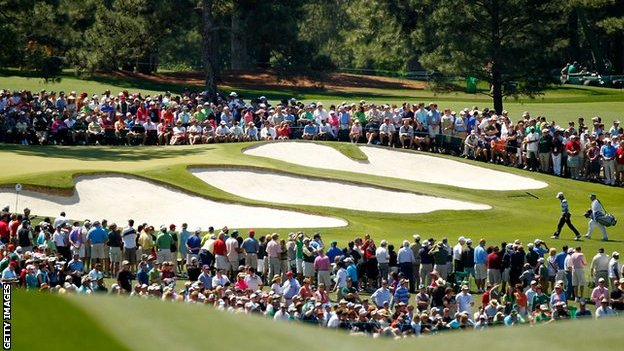 Spectators watch as Charl Schwartzel and his caddie Greg Hearmon walk up the seventh hole at Augusta