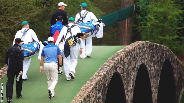 The caddies of Mike Weir, Garrick Porteous and Jason Day walk over Hogan's Bridge on the 12th hole during practice