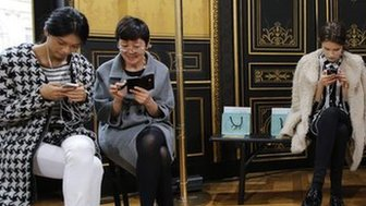A group of four women check their smart phones