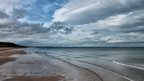 A wide beach with people walking on it. Clouds dominate in a blue sky above.
