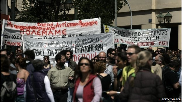 Protesters carry banners as they march towards Parliament during a labour strike on 09/04/14 in Athens, Greece.
