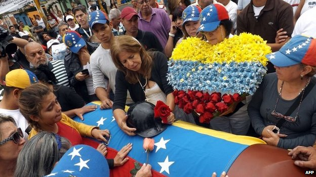 Relatives of Jimmy Vargas, a student who died during a recent protest, weep beside his coffin during his funeral in San Cristobal, 660 km from Caracas, February 26, 2014