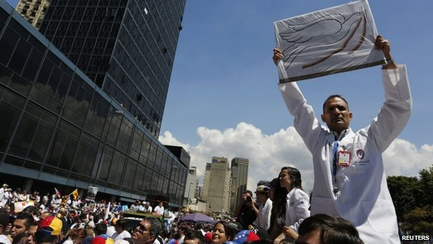 An anti-government doctor holds up a placard with a picture of a peace dove during a march to demand medical supplies for hospitals in Caracas on 10 March, 2014