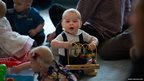 Britain's Prince George plays with toys during a Plunket nurse and parents group visit at Government House in Wellington, New Zealand