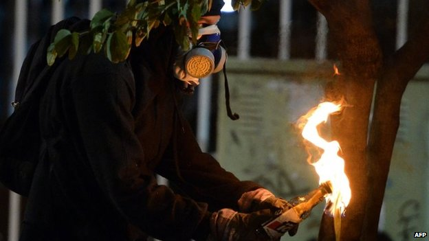 An anti-government activist gets ready to throw a Molotov cocktail during a protest in Caracas on 31 March, 2014