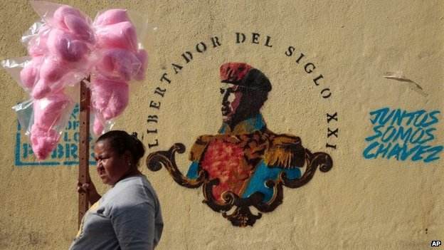 A cotton candy vendor stands next to a mural of Venezuela's late President Hugo Chavez on 22 March, 2014