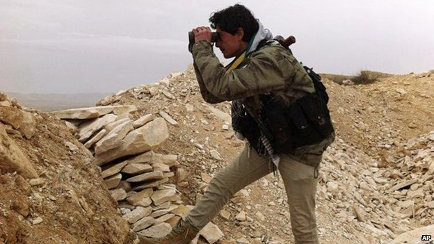 A Syrian rebel looks through his binocular at one of the frontlines of Yabroud town (13 March 2014)