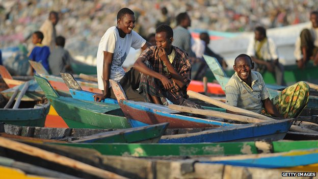 Somali fishermen sit next to their boats