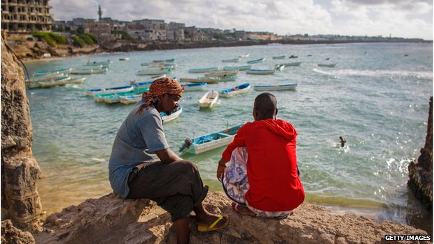 Somali fishermen look at the Mogadishu harbour