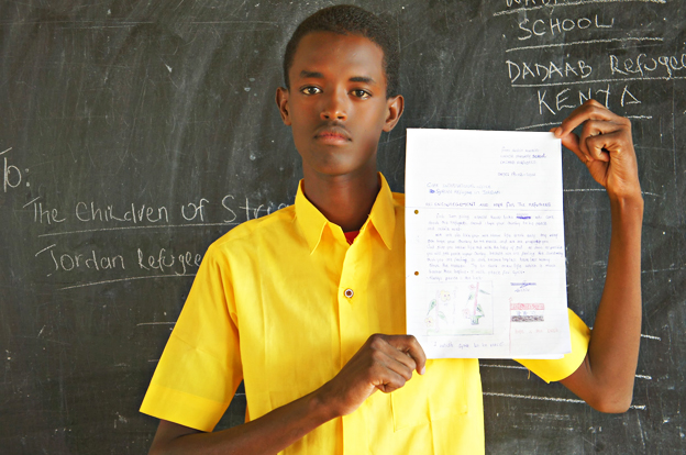 Abshir Hussein holding up his letter while wearing a yellow shirt