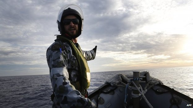 This handout photo taken on 7 April 2014 shows Able Seaman Boatswain's Mate Cameron Grant directing the boat coxswain on a Rigid Hull Inflatable Boat (RHIB) of HMAS Perth while searching for debris from missing Malaysia Airlines flight MH370 in the southern Indian Ocean