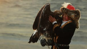 The young Mongolian girl Ashol-Pan cuddling her golden eagle