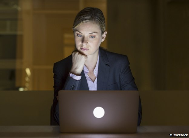 Woman looks at computer late at night