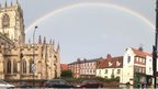 A large church to the left of the picture. A rainbow arches over buildings to the right.