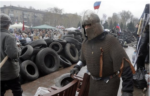 A pro-Russia activist dressed as a knight guards a barricade outside the regional state administration building in Donetsk on 10 April