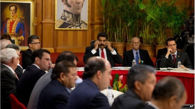 Venezuelan President Nicolas Maduro, top centre, looks toward leaders of the opposition at the start of a meeting at Miraflores presidential palace in Caracas, Venezuela, 10 April