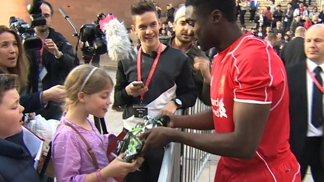 Liverpool defender Kolo Toure hands his football boots to a young fan at the launch of Liverpool's new kit on Thursday.