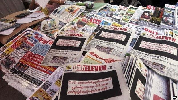 """A vendor sits by local weekly news journals with their front pages printed black with letters saying """"By opposing recent arrest and sentencing of journalists including a video journalist of DVB (Democratic Voice of Burma)"""" at a roadside shop Friday, 11 April 2014, in Yangon, Myanmar"""