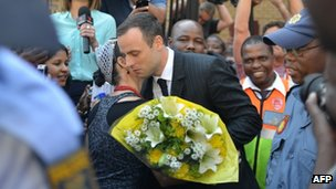 A woman hugs South African Paralympic track star Oscar Pistorius after handing him flowers as he leaves the North Gauteng Hight Court in Pretoria on 11 April 2014