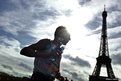 A runner sprays water on himself as he takes part of the 38th Paris Marathon, France.
