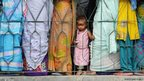 Indian voters wait in line outside a polling station in Dibrugarh