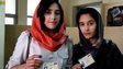 Two young female voters show of their voting ID cards in a Kabul polling station