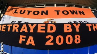 Luton Town fans display a banner