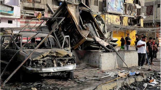 Iraqi civilians begin to clean up in the aftermath of a car bombing in Baghdad's eastern neighbourhood of Sadr City on Thursday.