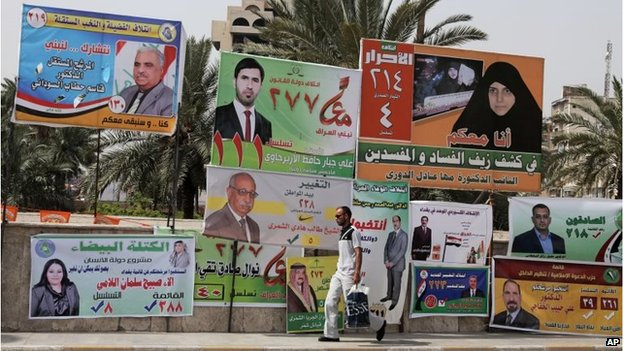 A man walks past election campaign posters in Baghdad on 7 April