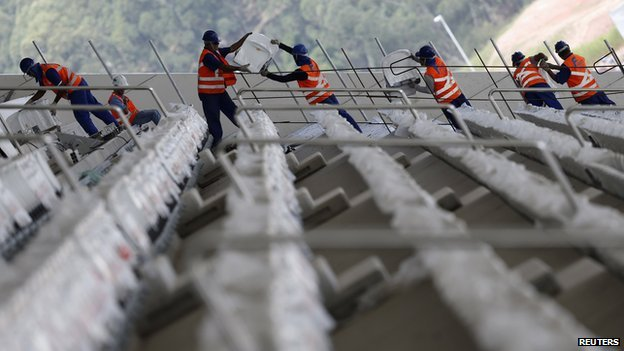 Labourers carry seats as they work on the construction of the Arena de Sao Paulo Stadium, one of the venues for the 2014 World Cup, in the Sao Paulo district of Itaquera on 11 April 2014.