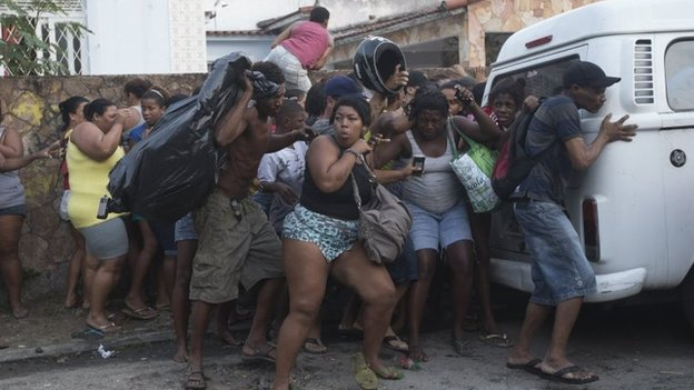 Squatters take cover from stun grenades and tear gas during an eviction in Rio de Janeiro, April 11, 2014