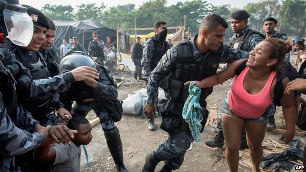A woman protests when a relative (L) is arrested by police, sent to evict squatters who were occupying an abandoned lot in Rio de Janeiro, on April 11, 2014.
